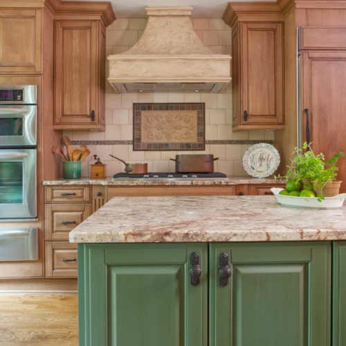 Warm wood finishes, bronze fixtures, stone counter tops, and leaded glass door.