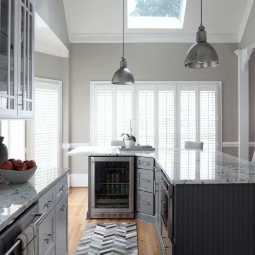 Clean, white kitchen with granite counter tops, subway tiles, and decorative mosaic tile